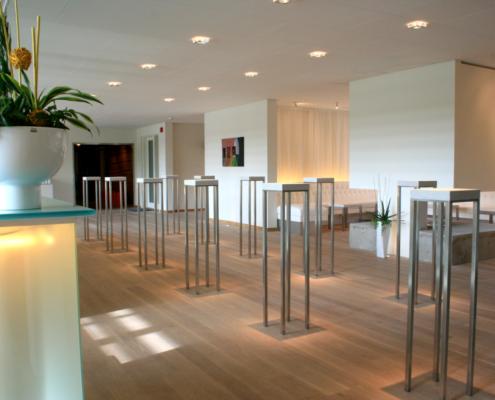 miljöbild, mingelplats med ståbord och trevlig belysning i ljust rum