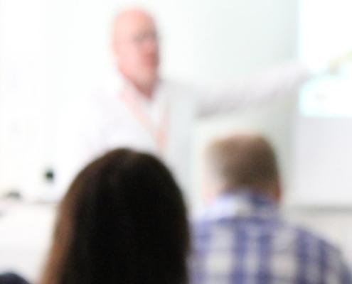 bild från föreläsning, huvuden bakifrån samt föreläsare. Suddig