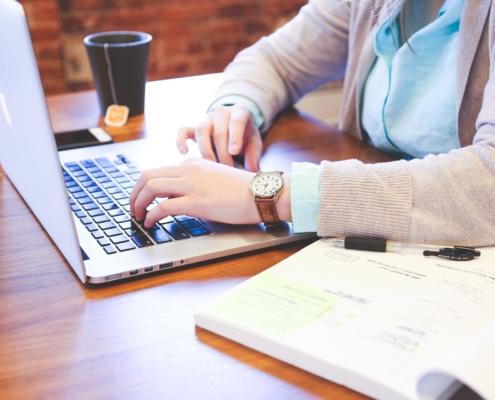 persons armar vid laptop, mugg med te bredvid.